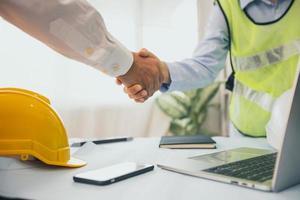 affärsman och byggnadsarbetare som skakar hand bredvid bärbar dator och hård hatt foto