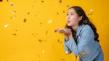 asiatisk kvinna som blåser färgglada konfetti ur händerna på gul bakgrund foto