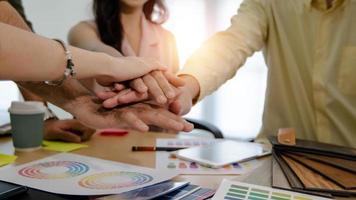 staplade händer över färgglada diagram på papper vid ett kontorsskrivbord foto