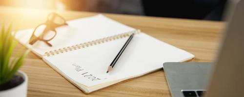 närbild av anteckningsboken med ord 2021 plan skriven bredvid penna, glasögon och bärbar dator