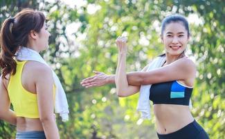 två vackra kvinnor som tränar utomhus i parken foto