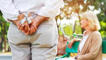 äldre man överraskar partner med en presentask