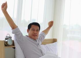 ung asiatisk man vaknar på morgonen frisk foto