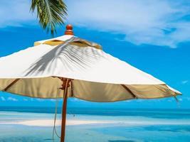 vitt paraply vid havet foto