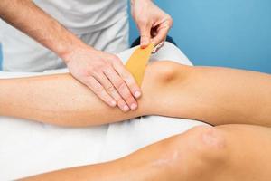 kinesio taping knä applicering av en sjukgymnast foto
