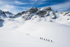 grupp klättrare ropade till toppen foto