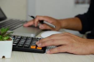 person som använder en miniräknare vid ett skrivbord foto