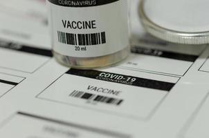 läkemedelsetiketter och flaskor med covid-19-vacciner