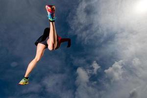 atletisk flicka hoppar medan du springer i bergen foto