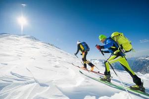 längdskidåkning team leder mot toppen av berget foto