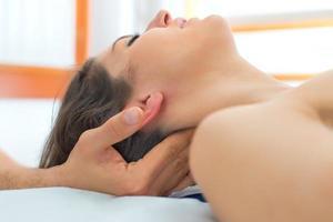 terapeut som masserar kvinnans nacke foto
