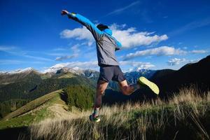 en idrottsman under en utförsåkning på bergsterräng foto