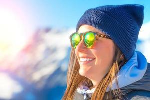 kvinnlig skidåkare med skidor som ler och bär skidglasögon foto
