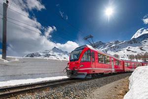 schweiziska bergståg korsar alperna med snövägg foto