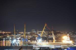 nattstadslandskap med utsikt över en hamn och horisont i bakgrunden i Vladivostok, Ryssland foto