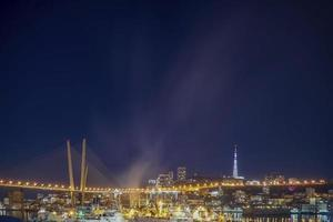 nattstadslandskap av den gyllene bron i Vladivostok, Ryssland foto