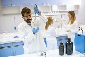 unga forskare i skyddande arbetskläder som står i laboratoriet och analyserar kolven med vätska foto