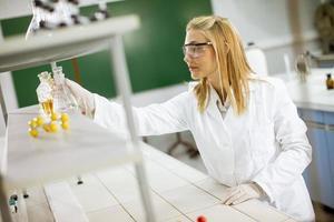kvinnlig medicinsk eller vetenskaplig forskare som tittar på kolvar med lösningar i ett laboratorium foto