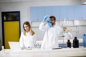 forskare som arbetar med blå vätska vid laboratorieglas foto