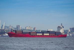 marinmålning med ett rött containerfartyg och stadssilhuett i bakgrunden i Vladivostok, Ryssland foto