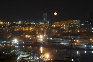 natt stadsbild med en kropp av vatten och gul måne i Vladivostok, Ryssland foto
