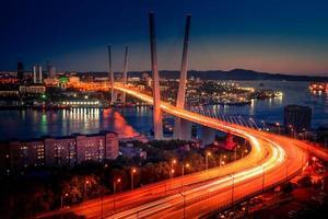 stadsbild med suddiga bilbelysning på den gyllene bron vid solnedgången i Vladivostok, Ryssland foto