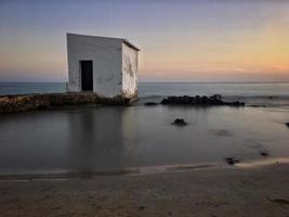 fiskarstuga vid solnedgången på några stenar nära stranden i Calpe, Alicante foto