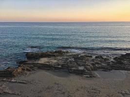 medelhavsstrand utan människor vid solnedgången i calpe, alicante foto