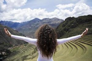 ung kvinna som tittar på Pisac Inca-ruiner i Peru foto