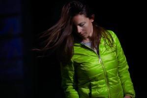 avslappnad tjej med grön vinterjacka och fritt hår foto