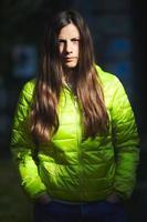 porträtt av en vacker kaukasisk flicka med långt brunt hår med grön vinterjacka foto