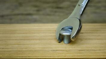 närbild av en skiftnyckel som skruvar in en mutter i en träplanka, utan att använda rätt verktygskoncept foto