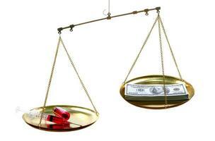 skalor med en medicinspruta på ena sidan och pengarsedlar på den andra på en vit bakgrund, dyrt behandlingskoncept