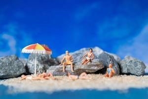 miniatyrfolk som bär baddräkter som kopplar av på stranden med en blå bakgrund, sommartid