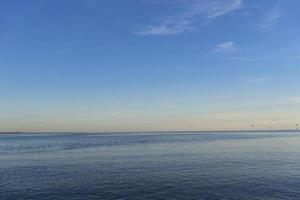 marinmålning av en vattenkropp med färgglad horisont och blå himmel foto