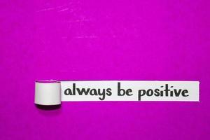 alltid vara positiv text, inspiration, motivation och affärsidé på lila sönderrivet papper