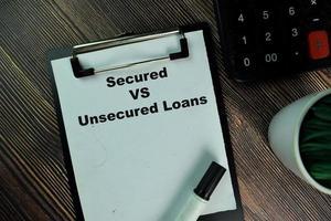 säkrade kontra lån utan säkerhet skrivna på pappersarbete isolerad på träbord