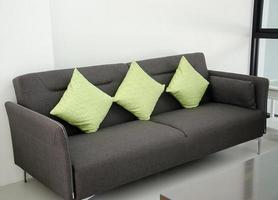 grå soffa med gröna kuddar