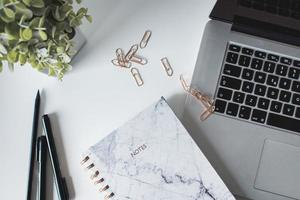 skrivbord med bärbar dator, anteckningsbok, penna, växt och gem