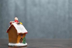 miniatyr jultomten sitter på ett tak, jul legend och glad semester koncept