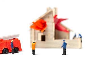 miniatyr brandmän tar hand om en brand nödsituation vid ett trähus