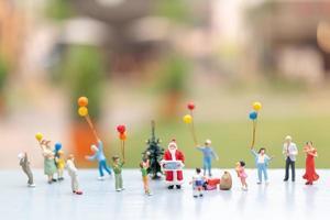 miniatyr Santa Claus håller gåvor för en lycklig familj, jul och gott nytt år koncept