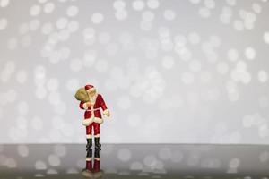 miniatyr jultomten bär en påse på en bokeh bakgrund, god jul och gott nytt år koncept.