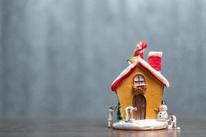 miniatyrfolk som målar ett hus och jultomten som sitter på taket, god jul och lycklig helgkoncept