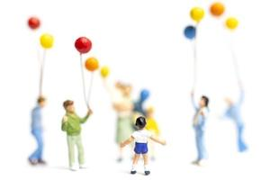 miniatyrbarn som håller ballonger på en vit bakgrund