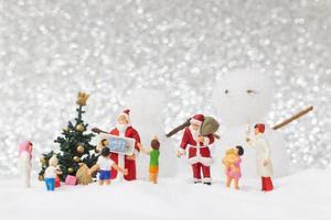 miniatyr jultomten och barn med en snö bakgrund, jul och gott nytt år koncept foto
