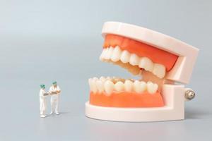 miniatyr tandläkare reparera mänskliga tänder med tandkött och emalj, hälsa och medicinska koncept foto