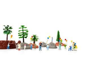 miniatyrfamilj som håller ballonger i parken, världens barns dagskoncept