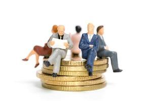 miniatyrföretagare som sitter på en stapel mynt, pengar och finansiella koncept