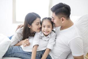 föräldrar och dotter omfamnar foto